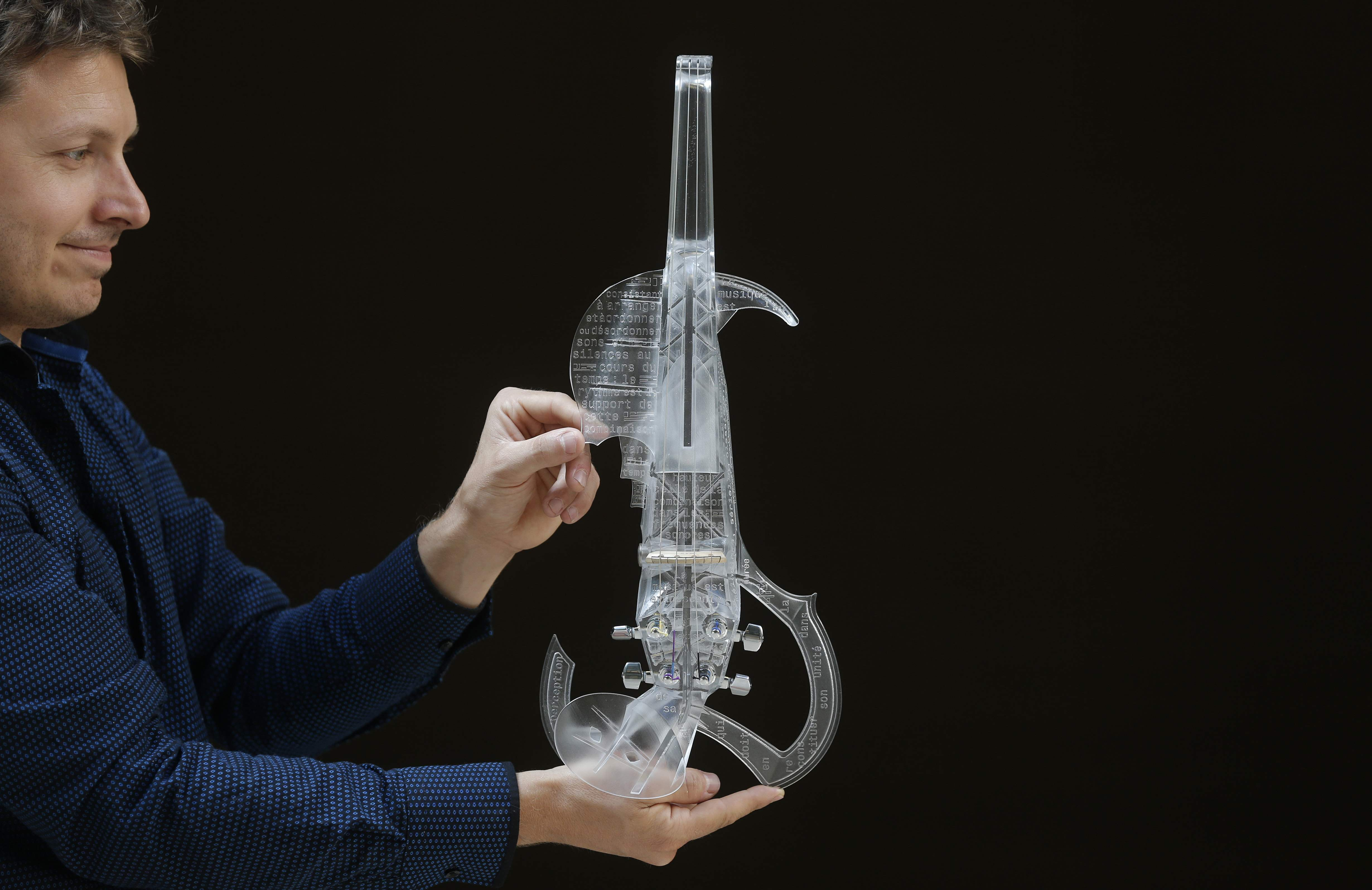 "French engineer and professional violinist Laurent Bernadac poses with the ""3Dvarius"", a 3D printed violin made of transparent resin, during an interview with Reuters in Paris, France, September 11, 2015. (Photo by Christian Hartmann/Reuters)"